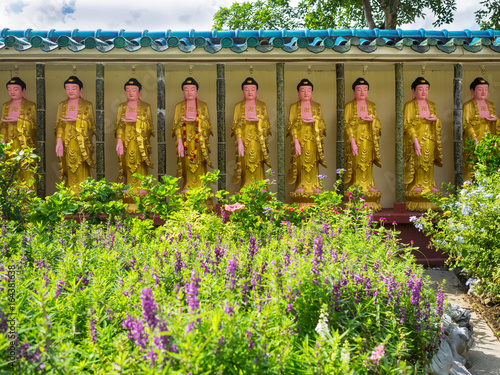A row of golden buddha statues with swastika symbol on their chests at Kek Lok Si temple in Georgetown, Penang, Malaysia