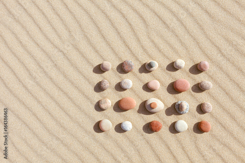 Pattern of colored pebbles on clean sand. Zen background, harmony and meditation concept