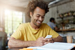 Cheerful handsome young African American male student in yellow t-shirt browsing internet on smart phone, having rest at coffee shop after classes at university, looking at screen and smiling broadly