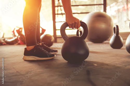 Póster Fitness training with kettlebell in sport gym with sunlight effect