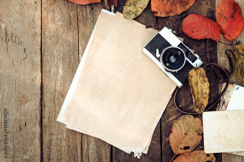 Retro camera and empty old instant paper photo album on wood table with maple leaves in autumn border design - concept of remembrance and nostalgia in fall season. vintage rustic style. © jakkapan