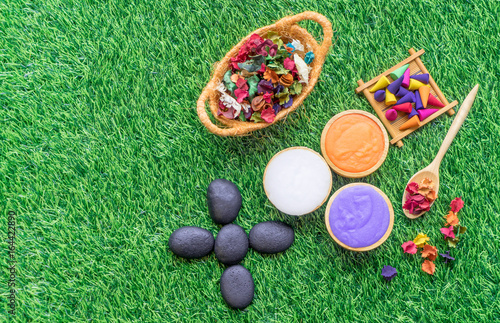 Colorful spa objects flat lay on green grass copy space