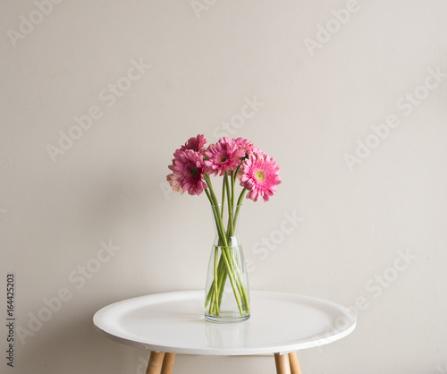 Aluminium Gerbera Pink gerberas in glass vase on small white round table against neutral wall background