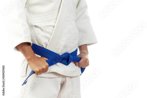 Close-up of a man fighter in a white kimono for judo, Jiu Jitsu ties up a blue b Poster