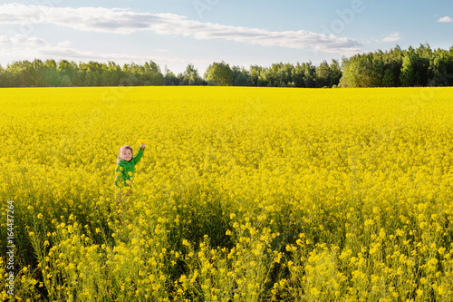 Fotobehang Oranje happy little girl with in rape field