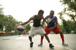 African american man friends playing on basketball court. Real authentic activity.