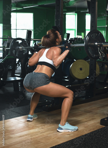 sporty girl squats with barbell training