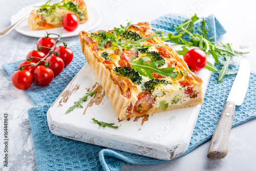 Delicious vegetarian homemade pie, Quiche with cherry tomatoes, broccoli and herbal cheese on old white cutting board. Healthy food concept. - 164449843