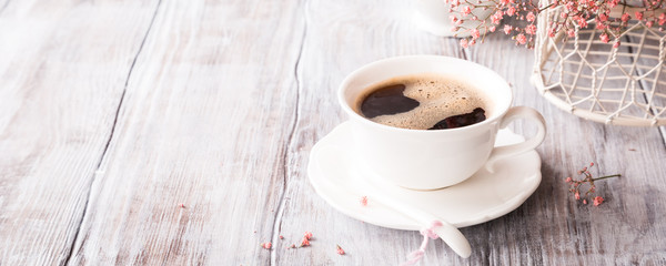 White cup of coffee with pink flowers on old white wooden background with copy space. © Iryna Melnyk