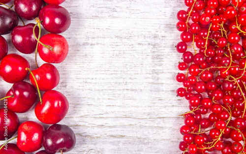Fresh ripe red currants and cherries on rustic wood background.