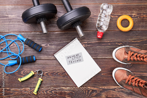 Set for sports on wooden background. Never stop trying to be stronger.