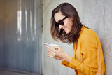 Joyful young woman texting and holding coffee while leaning against wall in urban outside setting - 164463475