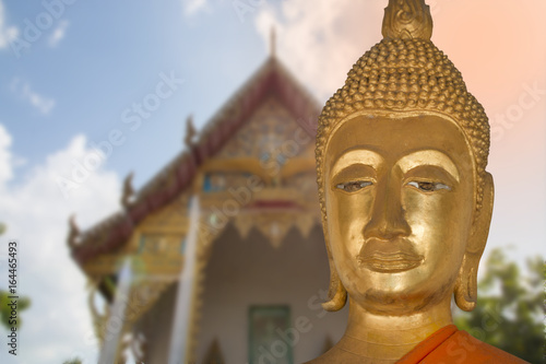 close up face of buddha with temple as background