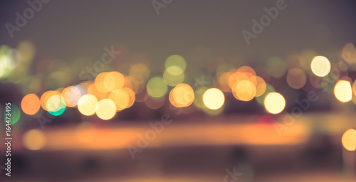 Wall mural Defocused blur of city lights at night abstract with vintage tone