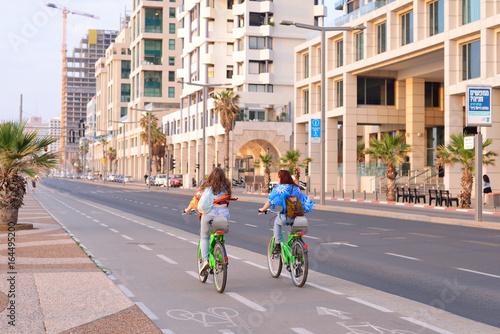 TEL AVIV, ISRAEL- APRIL, 2017: Herbert Samuel st. bike track and walking area for pedestrians in the center of Tel Aviv. Girls ride bicycles on holiday