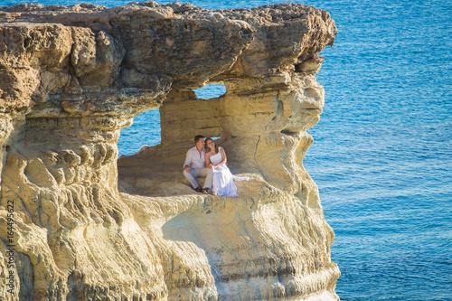 Plexiglas Cyprus beautiful gorgeous bride and stylish groom on rocks, on the background of a sea, wedding ceremony on cyprus