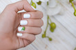 Beautiful female hand with white nail design
