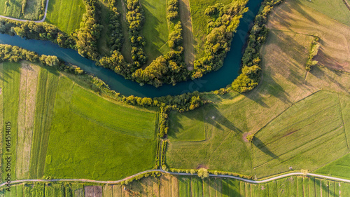 Papiers peints Cappuccino River bend surrounded by fields from bird's eye view.