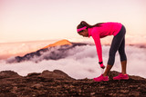 Trail runner woman tying running shoes laces getting ready to run on mountains nature in summer sunset dusk landscape. Nature outdoors.