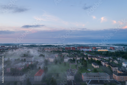 Aerial view of city in fog at amazing sunset. Summer nature landscape. © nikwaller