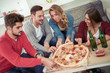 Group of young friends eating pizza and drinking beer