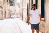 Hipster handsome male model with beard  wearing white blank  t-shirt with space for your logo or design in casual urban style - 164560835