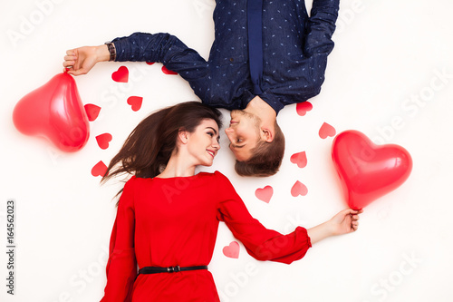 couple lies on a white background, holds balloons and looks at each other, view Poster