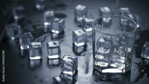 Slow motion. Close up pouring whiskey in glass with ice cubes.dark black background.