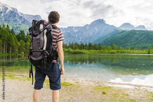 Hiking tourist from behind and lake near Alps in Almsee in Austria.