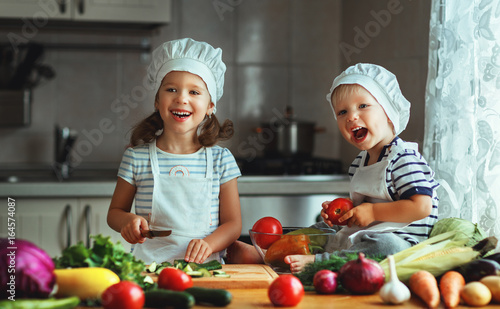 Healthy eating. Happy children prepares  vegetable salad in kitchen - 164574087