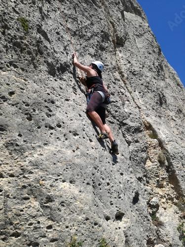 Mujer escalando por montaña rocosa en día de verano Poster