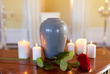 red rose and cremation urn with burning candles - 164599078