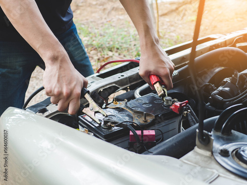 Charging car battery with electricity trough jumper cables Poster