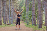 The sports girl raised her hands in the forest.