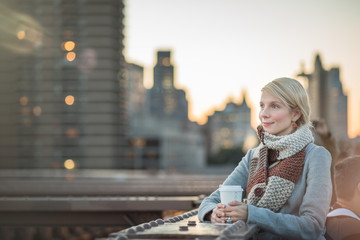 Woman on the Brooklyn Bridge Looking at Manhattan with a Coffee