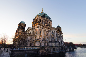 The main church Berliner Dom (Berlin, Germany), a landmark, is lit at sunrise, viewed from across the Spree river.