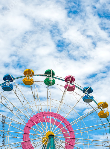 Fotobehang Amusementspark Colorful ferris wheel over blue sky.
