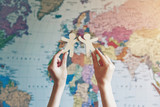 Hands holding wooden little men on map background. Symbol of friendship, partnership or cooperation between countries