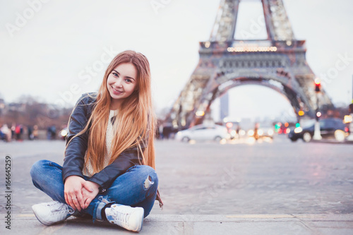 Fridge magnet smiling happy beautiful woman tourist in Paris looking at camera, portrait of caucasian girl near Eiffel Tower