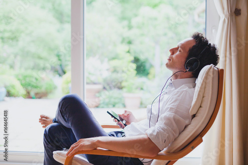 Leinwanddruck Bild listening relaxing music at home, relaxed man in headphones sitting in deck chair in modern bright interior