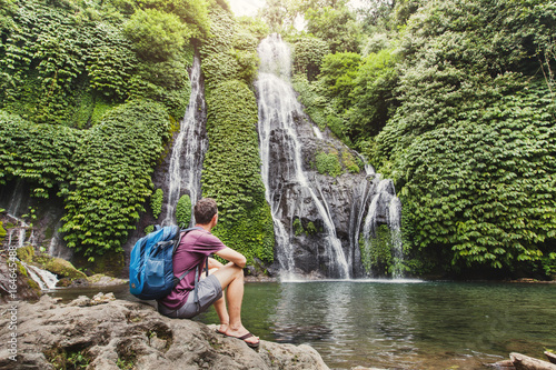 tourist backpacker looking at waterfall in Bali