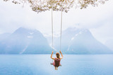 dream concept, beautiful young woman on the swing in fjord Norway, inspiring landscape - 164645853
