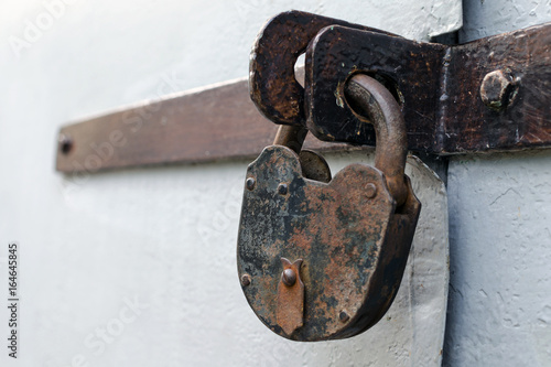 Old rusty but reliable barn door lock - the concept of prohibition or protection Poster