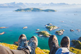 trekking shoes on feet of couple of travelers hikers sitting on top of the mountain in Norway with the beautiful view, trekkers selfy with norwegian landscape - 164646278
