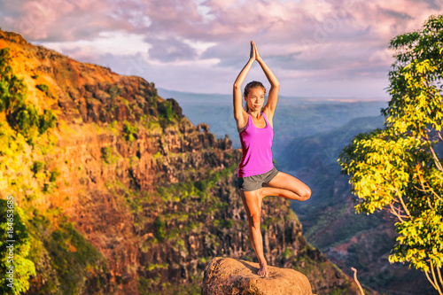 Fotobehang Purper Yoga girl doing tree pose on mountain nature landscape in Waimea Canyon, Kaui, Hawaii doing Vriksasana one leg standing. Woman practicing meditation in sunset, health and wellness concept.