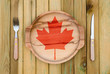 Concept of Canadian cuisine. Wooden plate with a Canada flag, fork and knife on a wooden background