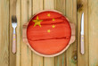 Concept of Chinese cuisine. Wooden plate with a China flag, fork and knife on a wooden background