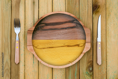 Concept of Ukrainian cuisine. Wooden plate with a Ukraine flag, fork and knife on a wooden background