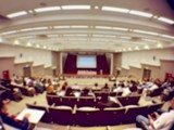 blurred image of Business Conference and Presentation. People Meeting Conference Seminar, Audience at the conference hall. - interior of a conference hall, warm & vintage tone photo.