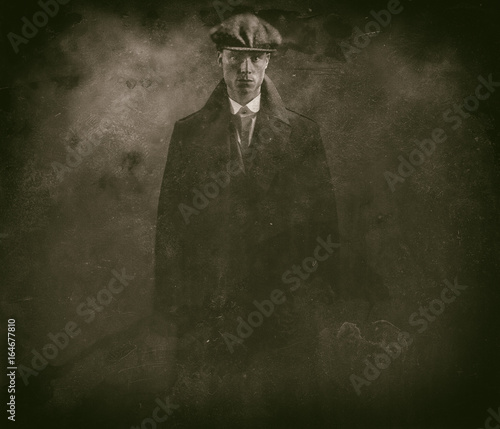 Antique wet plate photo of threatening 1920s english gangster in smoky room.